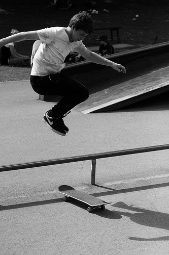 skateboarder doing hippie jump over obstacle